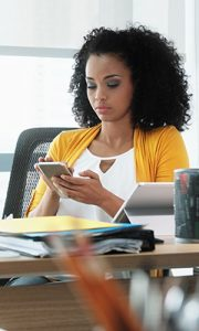 Employee distracted in office meeting by her phone