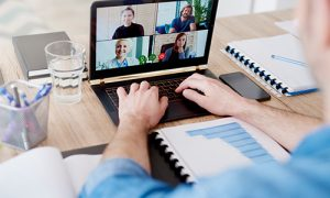 Man working remotely and video chatting with his coworkers