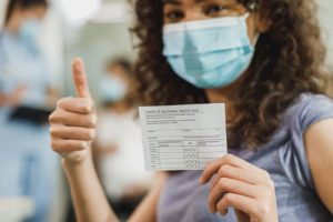 employee wearing mask holding required covid vaccine card giving thumbs up